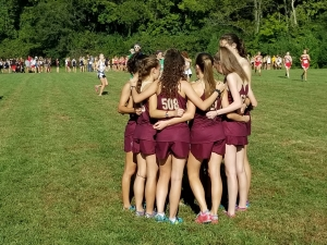 Varsity girls gather together for encouragement before their race at the Milford Invitational