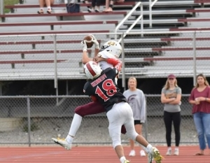 Will Schroeder making athletic catch over Milford defender